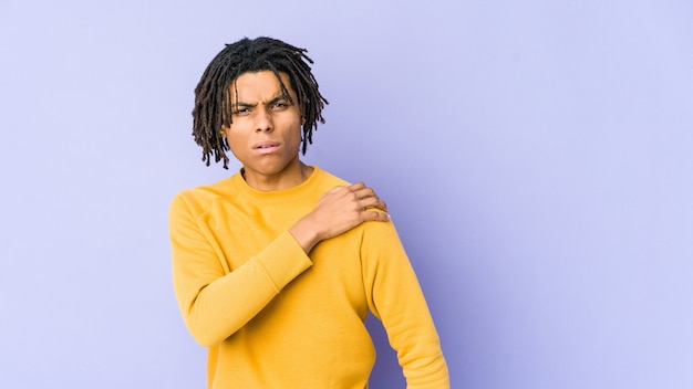 Junger schwarzer mann, der rasta-frisur trägt, die schulterschmerzen hat.