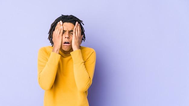 Junger schwarzer mann, der rasta-frisur trägt, die trostlos jammert und weint.