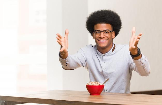Junger schwarzer mann, der sehr glücklich frühstückt, der front eine umarmung gebend