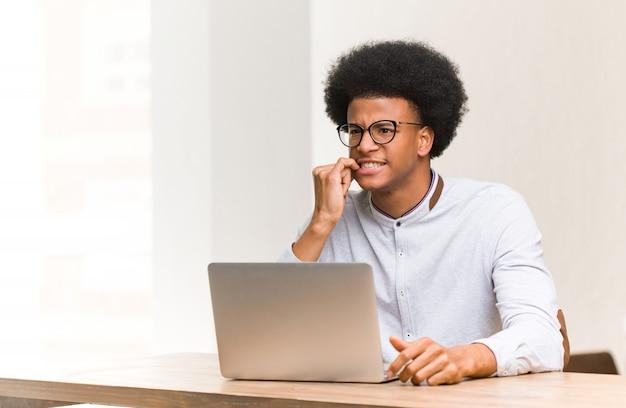 Junger schwarzer mann, der seine beißenden nägel des laptops, nervös und sehr besorgt verwendet