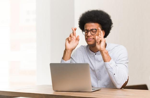 Junger schwarzer mann, der seine laptopüberfahrtfinger für das haben des glücks verwendet