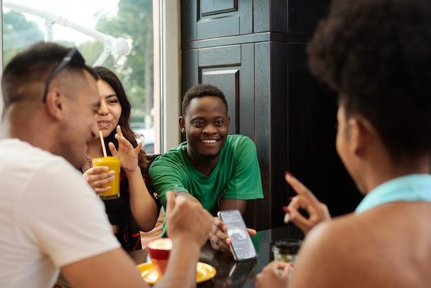 Junger schwarzer mann, der seinen freunden drinnen telefonbildschirm zeigt