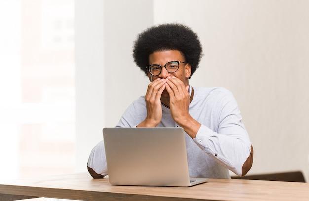 Junger schwarzer mann, der seinen laptop benutzt, der über etwas lacht und mund mit händen bedeckt