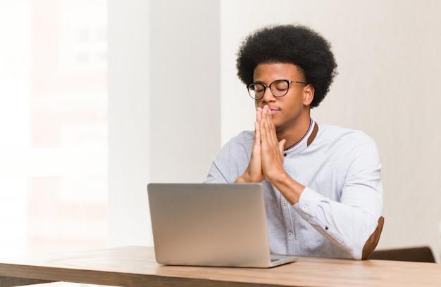 Junger schwarzer mann, der seinen laptop betet sehr glücklich und überzeugt verwendet