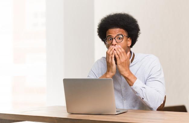 Junger schwarzer mann, der seinen laptop sehr erschrocken und ängstlich versteckt verwendet