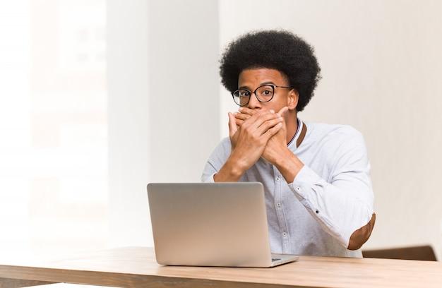 Junger schwarzer mann, der seinen laptop überrascht und entsetzt verwendet