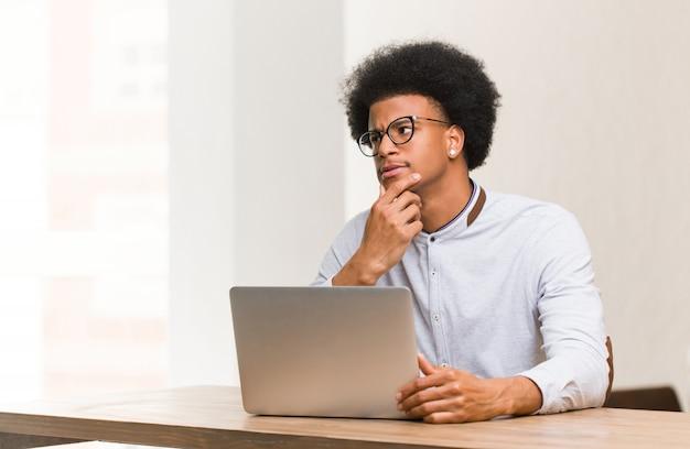 Junger schwarzer mann, der seinen laptop zweifelnd und verwirrt verwendet