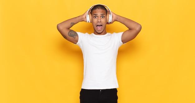 Junger schwarzer mann, der sich gestresst, besorgt, ängstlich oder verängstigt fühlt, mit händen auf dem kopf, die bei einem fehler in panik geraten