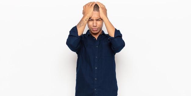 Junger schwarzer mann, der sich gestresst und ängstlich, depressiv und frustriert mit kopfschmerzen fühlt und beide hände zum kopf hebt
