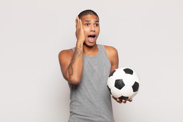 Junger schwarzer mann, der sich glücklich, aufgeregt und überrascht fühlt und mit beiden händen im gesicht zur seite schaut