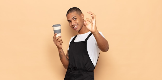 Junger schwarzer mann, der sich glücklich, entspannt und zufrieden fühlt, zustimmung mit okayer geste zeigt und lächelt