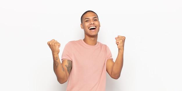Junger schwarzer mann, der sich glücklich, positiv und erfolgreich fühlt und sieg, erfolge oder viel glück feiert