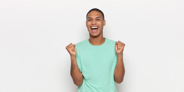 Junger schwarzer mann, der sich schockiert, aufgeregt und glücklich fühlt, lacht und erfolg feiert und wow sagt!