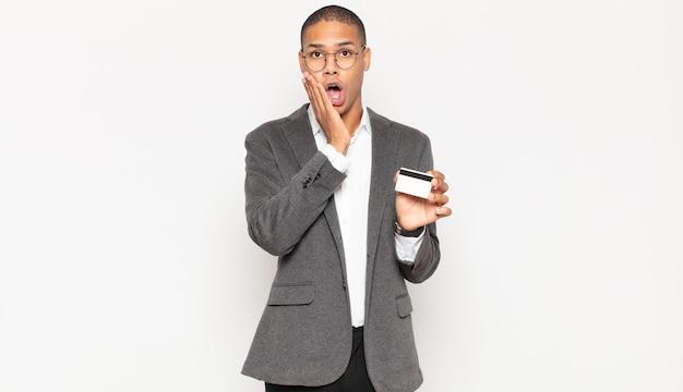 Junger schwarzer mann, der sich schockiert und ängstlich fühlt und mit offenem mund und händen auf den wangen erschrocken aussieht