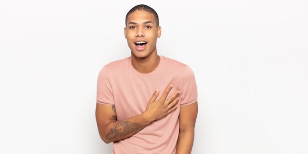 Junger schwarzer mann, der sich schockiert und überrascht fühlt, lächelt, hand zu herzen nimmt, glücklich ist, derjenige zu sein oder dankbarkeit zu zeigen