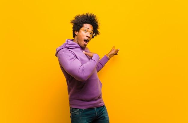 Junger schwarzer mann, der sich schockiert und überrascht fühlt und auf den kopierraum an der seite mit erstauntem, offenem blick gegen die orangefarbene wand zeigt