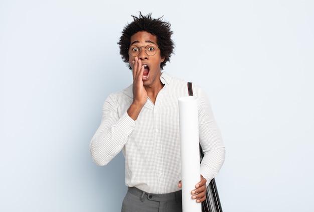 Junger schwarzer mann, der sich schockiert und verängstigt fühlt und mit offenem mund und händen auf den wangen erschrocken aussieht