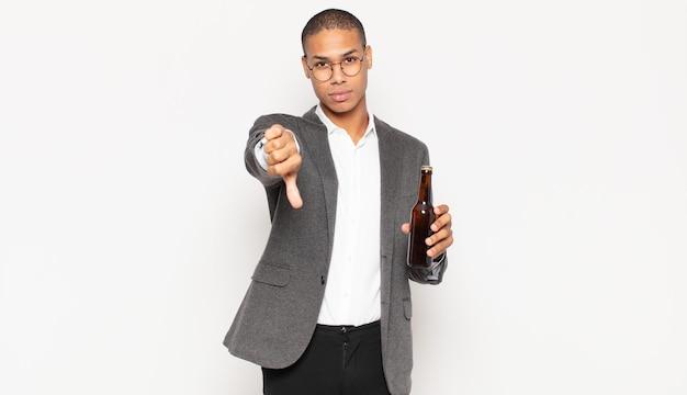 Junger schwarzer mann, der sich verärgert, wütend, verärgert, enttäuscht oder unzufrieden fühlt und mit ernstem blick daumen nach unten zeigt