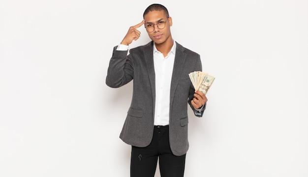 Junger schwarzer mann, der sich verwirrt und verwirrt fühlt und zeigt, dass sie verrückt, verrückt oder verrückt sind