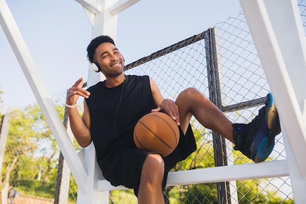 Junger schwarzer mann, der sport macht, basketball, aktiven lebensstil, sommermorgen spielt, glücklich lächelt, spaß hat, musik auf kopfhörern zu hören