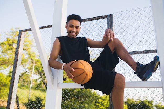 Junger schwarzer mann, der sport treibt, basketball spielt, aktiven lebensstil, sommermorgen, lächelnd glücklich, spaß zu haben