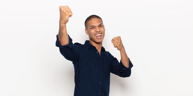 Junger schwarzer mann, der triumphierend schreit, wie aufgeregter, glücklicher und überraschter gewinner aussieht und feiert