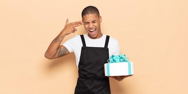 Junger schwarzer mann, der unglücklich und gestresst aussieht, selbstmordgeste, die waffenzeichen mit hand macht, zeigt auf kopf