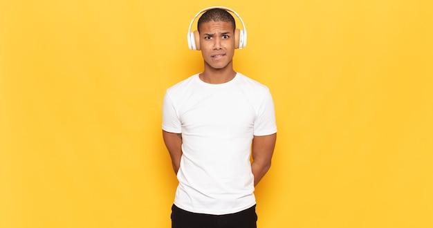 Junger schwarzer mann, der verwirrt und verwirrt aussieht, mit einer nervösen geste auf die lippe beißt und die antwort auf das problem nicht kennt