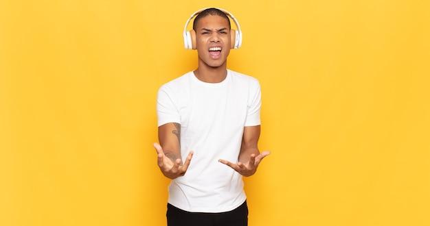 Junger schwarzer mann, der wütend, genervt und frustriert schreiend wtf aussieht