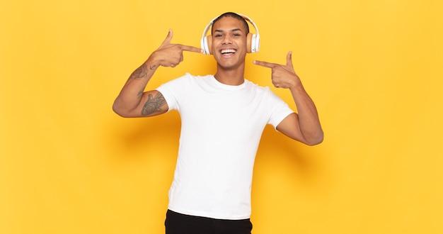 Junger schwarzer mann, der zuversichtlich lächelt und auf eigenes breites lächeln zeigt, positive, entspannte, zufriedene haltung