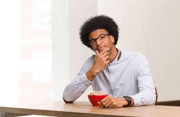 Junger schwarzer mann, der zweifelnd und verwirrt frühstückt