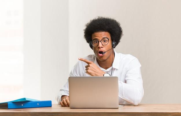 Junger schwarzer mann des telemarketers, der auf die seite zeigt