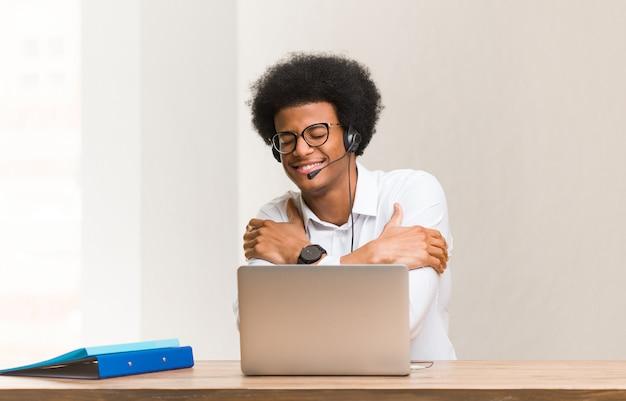 Junger schwarzer mann des telemarketers, der eine umarmung gibt