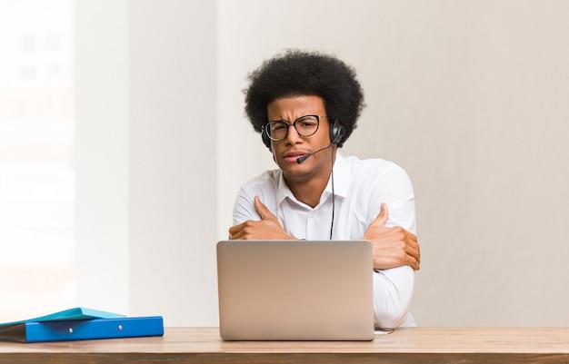 Junger schwarzer mann des telemarketers, der wegen der niedrigen temperatur kalt wird