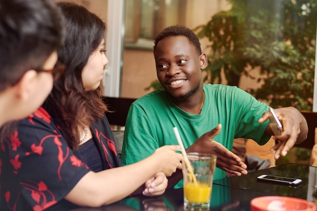 Junger schwarzer mann erklärt seinen freunden an einem tisch etwas