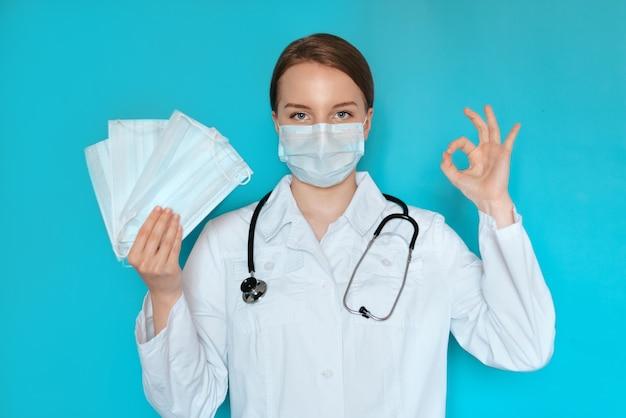 Junger schwarzer mann im medizinischen bereich, der einen weißen kittel und eine gesichtsmaske trägt und eine gesichtsmaske anbietet.
