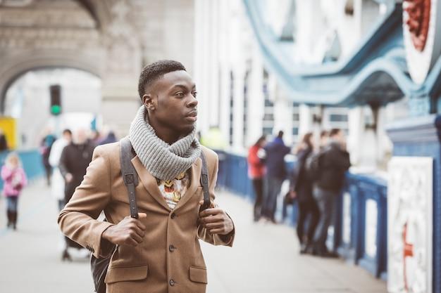 Junger schwarzer mann in london gehend auf kontrollturm-brücke