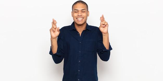 Junger schwarzer mann lächelt und kreuzt ängstlich beide finger, fühlt sich besorgt und wünscht oder hofft auf viel glück
