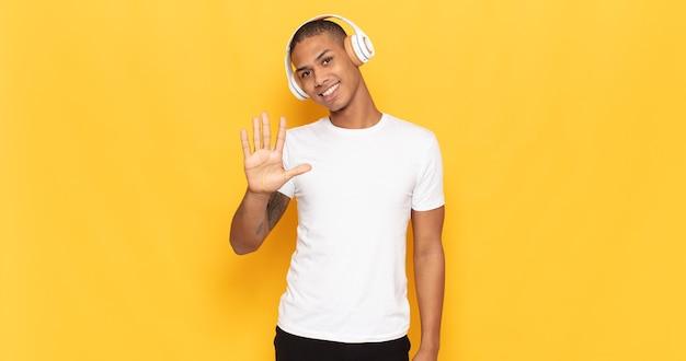 Junger schwarzer mann lächelt und sieht freundlich aus, zeigt nummer fünf oder fünften mit der hand nach vorne, countdown