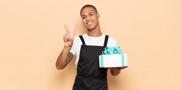 Junger schwarzer mann lächelt und sieht freundlich aus, zeigt nummer zwei oder sekunde mit der hand nach vorne, countdown