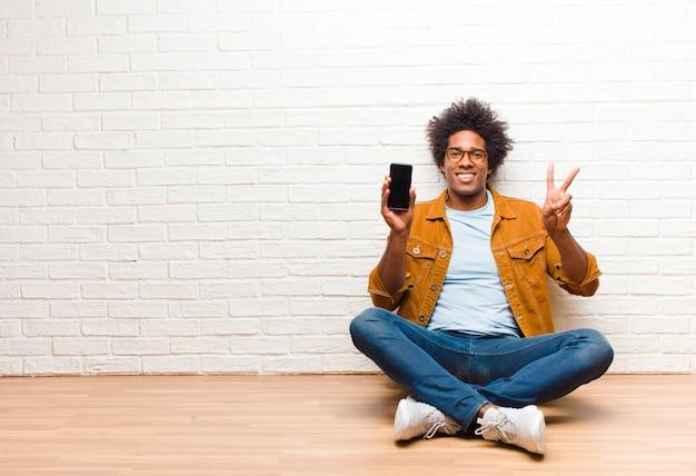 Junger schwarzer mann mit einem intelligenten telefon, das auf dem boden sitzt