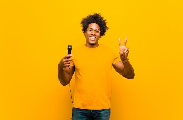 Junger schwarzer mann mit einem mikrofon singend