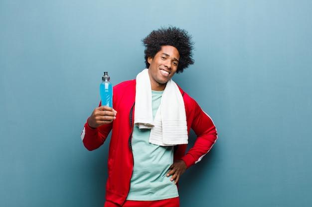 Junger schwarzer mann mit einem sportgetränk gegen blaue schmutzwand