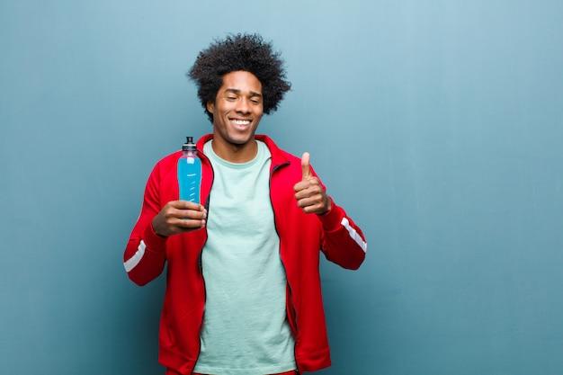 Junger schwarzer mann mit einem sportgetränk gegen blauen schmutz