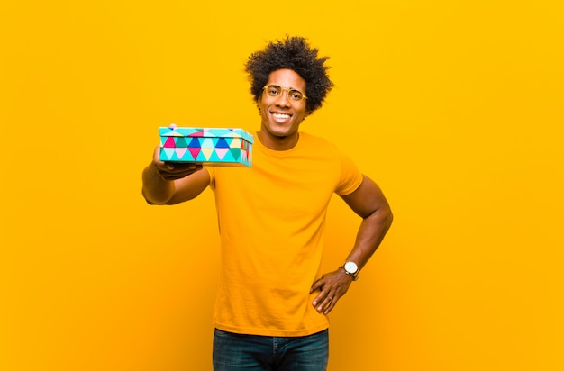 Junger schwarzer mann mit einer geschenkbox