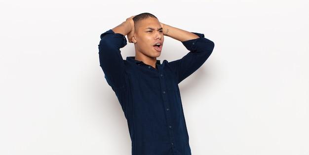 Junger schwarzer mann mit offenem mund, der wegen eines schrecklichen fehlers entsetzt und schockiert aussieht