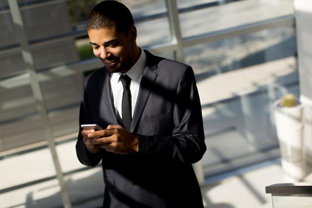 Junger schwarzer mann mit telefon im büro