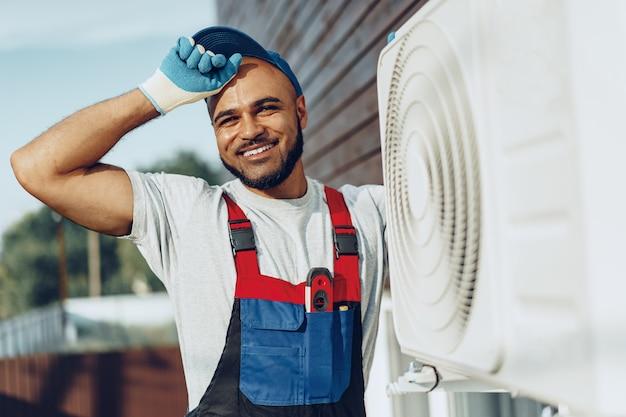 Junger schwarzer mann reparaturmann, der eine außenklimaanlage überprüft