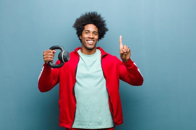 Junger schwarzer mann trägt mann mit einem dummkopf gegen blauen schmutz w zur schau