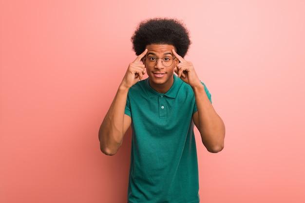 Junger schwarzer mann über einer rosa wand, die eine konzentrationsgeste tut